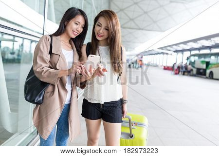 Women checking on cellphone in airport