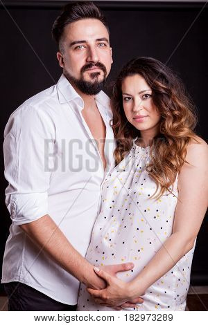 Pregnant woman with her husband in studio photo. Wife and husband. Parenthood and expecting baby