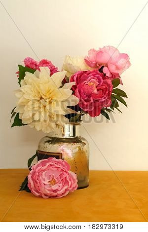 beautiful bouquet with artificial silk flowers peonies in the can white and yellow background.