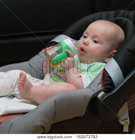 Newborn baby in a Car Seat drinking from bottle
