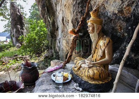 Stone figure of a Buddhist monk and offerings on the beach of a tropical island