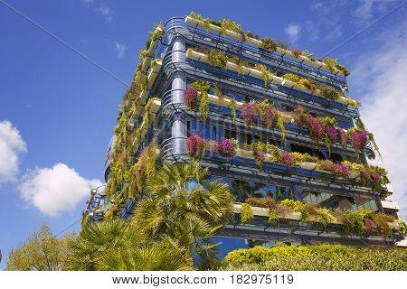 Beautiful modern building with growing house plants over beautiful blue sky
