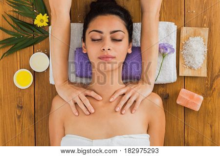 Massage in aroma spa wellness center, top view. Beautiful girl in cosmetology cabinet or beauty parlor.