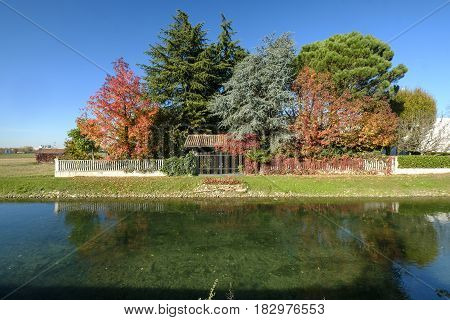 Garden along the bicycle path of the Martesana canal between Milan (Lombardy Italy) and the Adda river in november with the gorgeous colors of the fall