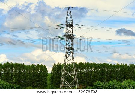 High voltage electrical pylon on a background of sky and forest, summer time