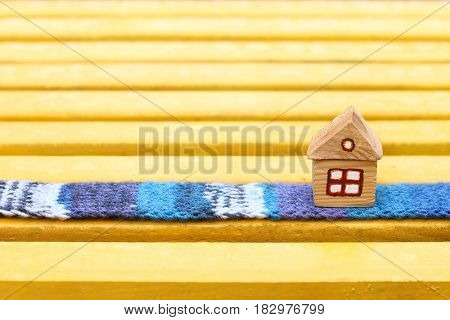 Small wooden house with a window stands on a blue scarf / Warm floor for comfort