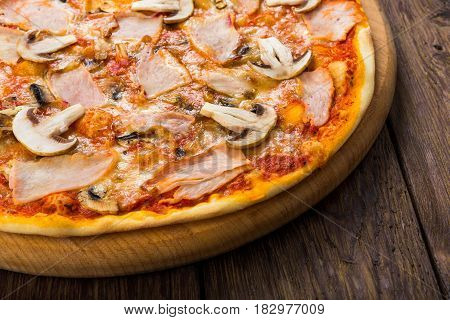 Delicious pizza with mushrooms and smoked chicken meat - thin pastry crust isolated at wooden background, with piece cut off