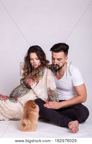 Happu pregnant woman with her husband and dog in studio photo. Wife and husband. Parenthood and expecting baby