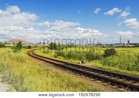 Industrial summer landscape. The railway runs through a field in the industrial area