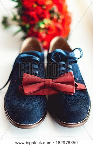 Close up of modern man accessories. Cherry bow tie, blue leather shoest and red wedding bouquet on a carpet. Set for formal style of wearing. Grooms wedding accesories