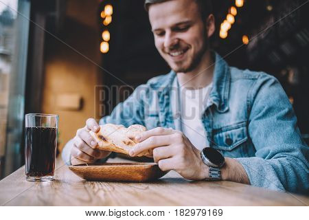 Young happy man sitting in a restaurant near window and eating a big tasty sandwich. Cute guy is hungry and going to have a nice bite