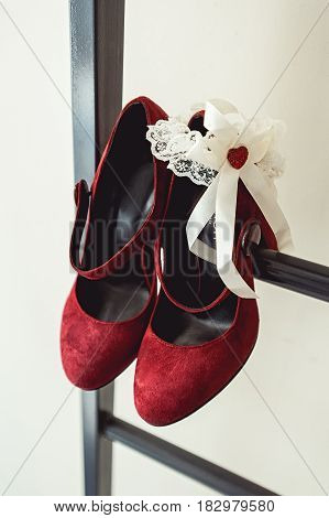 Ladies red chamois leather pumps shoes on a metal fire ladder at the balcony. brides accessories in a wedding day.