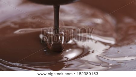 Slow motion of premium dark melted chocolate being poured from spoon in center part of frame, 4k photo