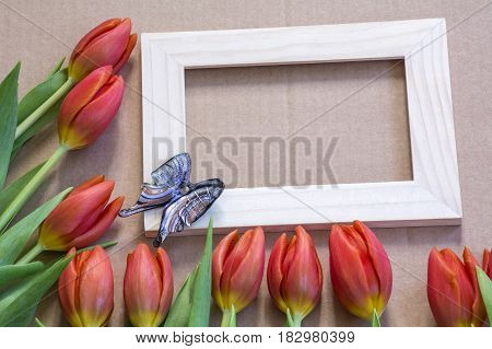 Blue glass butterfly on the wooden frame with many red tulips around