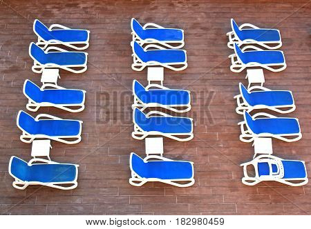 rows of blue deckchairs at a hotel swimming pool, waiting for guests