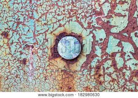 Old obsolete rusty metal surface with round rivet in the middle and cracked decay green paint as vintage corroded peeling wall background
