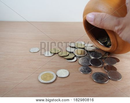 Thai baht coin saving money in baked clay jar on wooden background