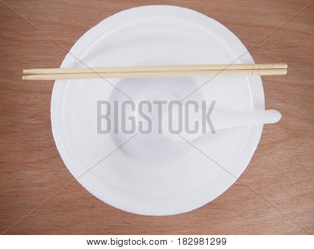 Empty disposable foam bowl with wooden chopsticks plastic spoon