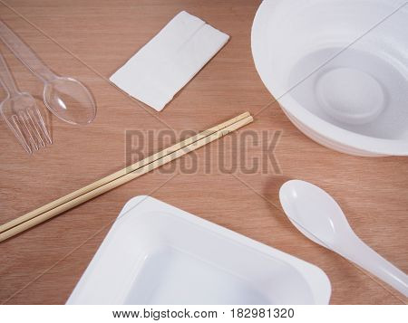 Disposable equipmentempty kitchen ware on wood background