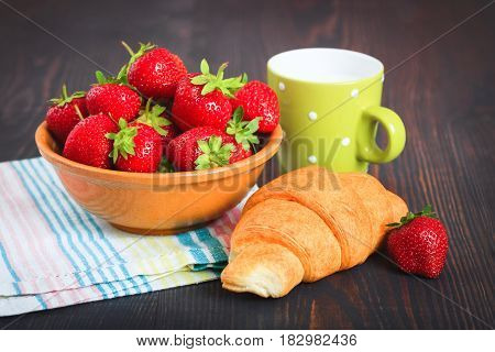 Plate with strawberry croissant and cup of milk on a wooden table. Breakfast in a rustic style.