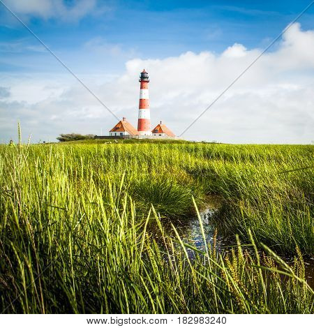 Beautiful Landscape With Small Pond And Lighthouse In The Background At North Sea In Nordfriesland,