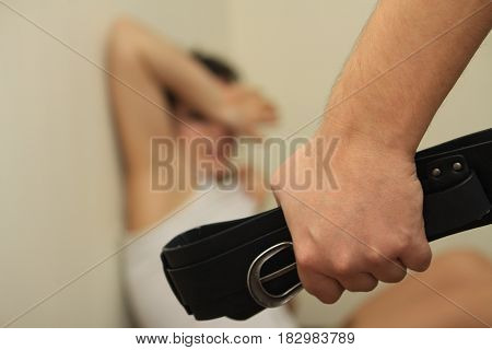 man's hand with a strap on the background of the terrified girl