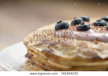 blini with yogurt and blueberries on wood table, sweet breakfast