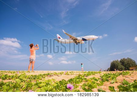 PHUKET THAILAND - MARCH 04 2017: Unidentified Mom and Son take photo the plane was landing phuket international airport near Mai Khao Beach on Phuket Island in Thailand.