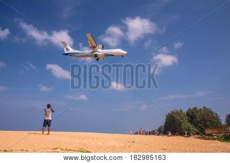 PHUKET THAILAND - MARCH 04 2017: Unidentified Man take photo the plane was landing phuket international airport near Mai Khao Beach on Phuket Island in Thailand.