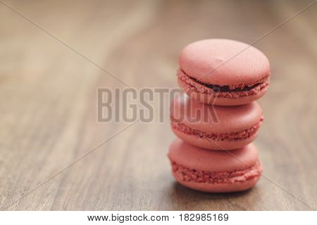 closeup shot stack of pastel colored macarons with strawberry flavour on wood table, vintage toned photo