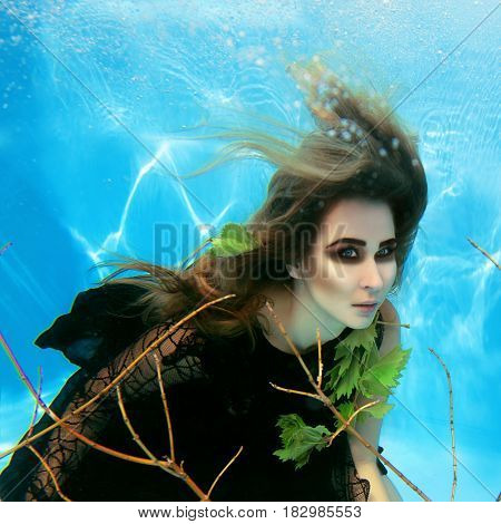 Underwater fashion portrait of beautiful blonde young woman in black dress with grape leaves
