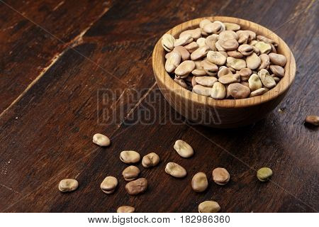 Dried fava beans in a wooden plate on a wooden background. Next to a plate beans are scattered on the table
