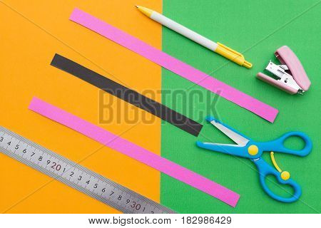 ruler scissors stapler and hand cut paper straps on colorful scrapbook