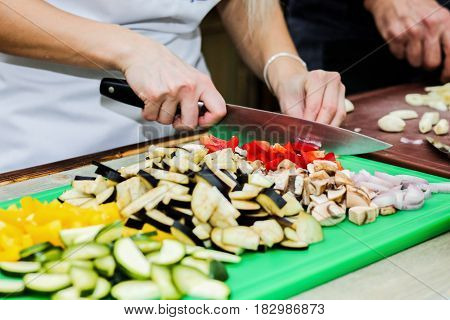 The chef in the kitchen prepares healthy food with vegetables.
