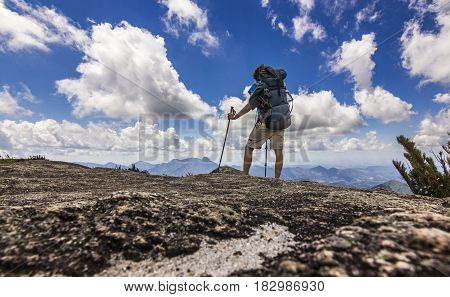man with backpack standing on top of brasil mountain with green forest and steep rocks with blue sky and clouds at daylight