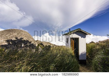 white little house in brasil mountains with green forest and steep rocks with blue sky and clouds at daylight
