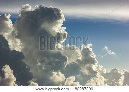 big cumulus clouds on sky at sunset befire storm