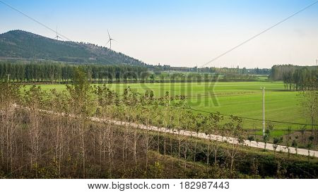 Image captured on High Speed Rail (HSR) from Tianjin to Shanghai, passing countryside with distant wind generators. Average speed: 300 km/h.