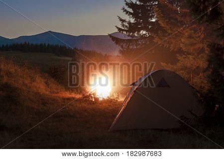 Hikers tent in mountains at evening with a bonfire with sparkles near it