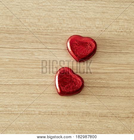 Chocolate heart wrapped in red on wood. valentine concept