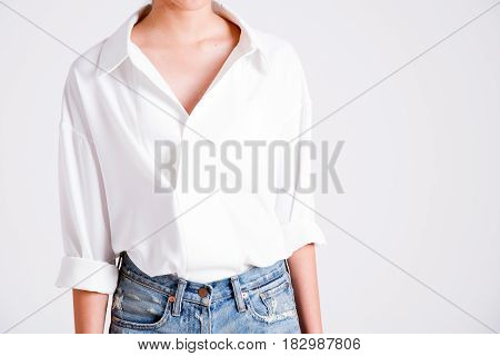 An Elegant Woman Stands In The Studio In A White Shirt With An Unbuttoned Top Button And Denim Short
