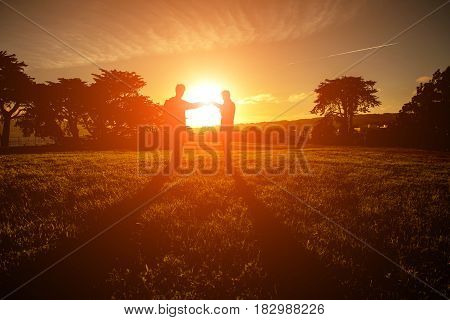 Silhouette Of Two Man Standing On Field During Sunset