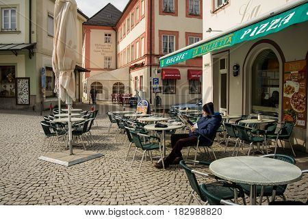Altoetting,Germany-April 23,2017: A man reads the newspaper while sitting on the terrace of a café