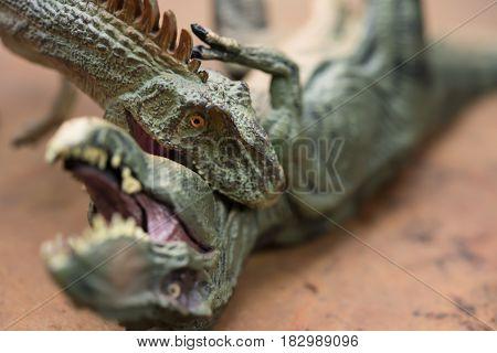 a allosaurus biting a tyrannosaurus toys horizontal
