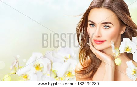 Beauty Woman with orchid flowers Portrait. Beautiful Spa Girl Touching her Face. Perfect Fresh Skin. Isolated on White Background. Pure middle aged Beauty Model. Youth and Skin Care Concept, aging