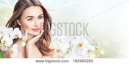 Beauty Woman with orchid flowers Portrait. Beautiful Spa Girl Touching her Face. Perfect Fresh Skin. On a White Background. Pure middle aged Beauty Model. Youth and Skin Care Concept, aging cosmetics