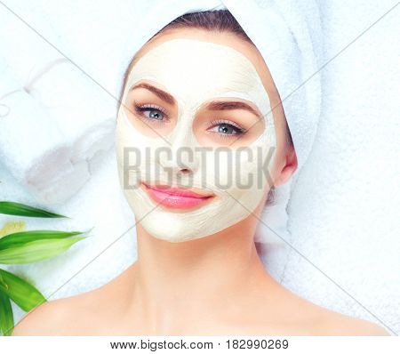 Spa Woman applying Facial clay Mask. Beauty Treatments. Close-up portrait of beautiful girl with a towel on her head applying facial mask. Skin care concept, cure, acne treatment