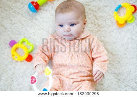 Cute adorable newborn baby playing with colorful rattle toy on white background. New born child, little girl looking on toy or camera. Family, new life, childhood, beginning concept