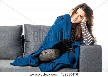 Young Woman Sitting On A Couch, Holding Her Head, Having A Strong Headache Covered Blanket