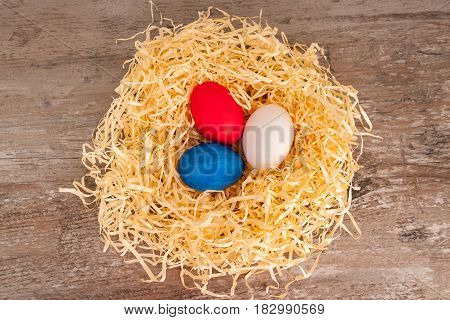 Easter tricolour eggs on a wooden background in the nest. Situated on the middle.